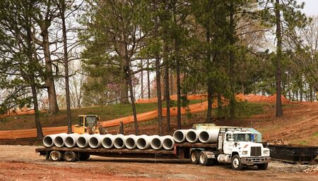 Concrete water pipes lined up on a flatbed truck