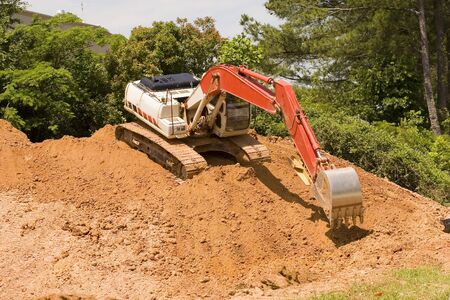 front end loader: An orange front end loader crawling down the face of a dirt pile Stock Photo