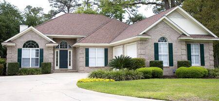 좋은 벽돌 집과 금이 콘크리트 드라이브 웨이와 함께 잘 된 잔디