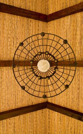 light fixture: A bamboo and wood roof with a wrought iron light fixture