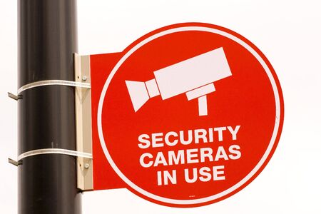 A red security camera sign on a black pole on white background photo