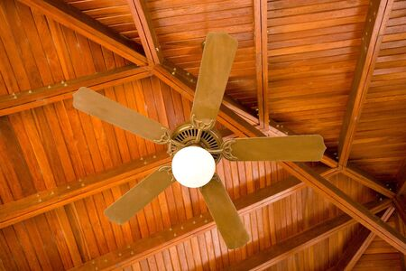 light fixture: A ceiling fan and light fixture under a wood pavilion roof