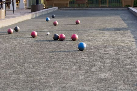 A bocce ball court with colored balls in early morning light