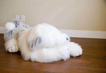 A large stuffed dog on a polished hardwood floor Reklamní fotografie