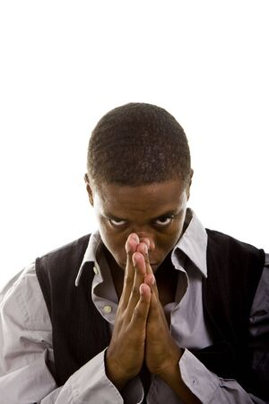 A young black man dressed in grey and black praying and looking at camera