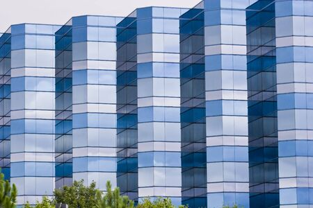 A modern blue and grey glass office building