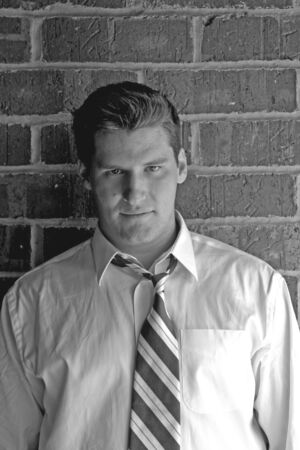 open collar: An athletic looking young man with tie and open collar against a brick wall