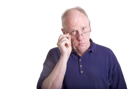 An older bald guy in a blue shirt with hand on glasses