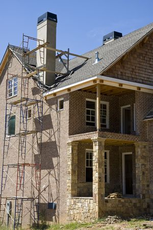 A new brick and stone home construction with scaffold Imagens