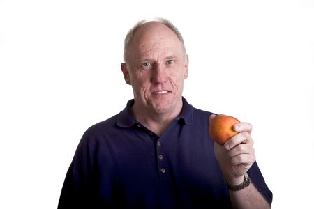 An older bald guy showing a fresh peach and smiling Stock Photo - 3703804