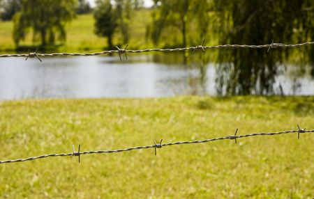 Strands of barbed wire in front of a lawn and a lake Stock Photo - 3708748