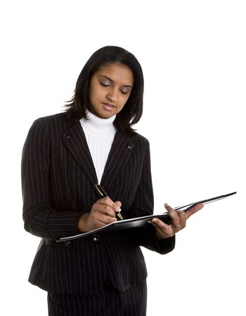 dark haired woman: A dark haired woman in business suit writing in a notebook