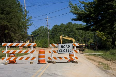 An old road closed for construction with heavy equipment in the background Imagens