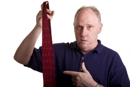 An older bald guy pointing to a tie with a question on his face Stok Fotoğraf