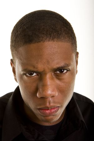 An angry young black man closeup looking at camera Stock Photo