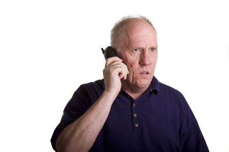 An older guy on a telephone looking mad or sad
