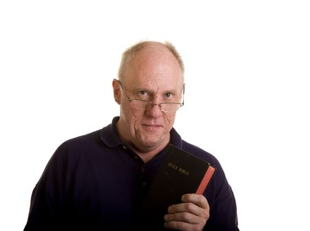 An older bald man holding a bible and looking over his reading glasses photo