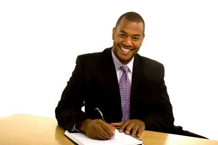 A black businessman in a suit sitting at a desk and writing looking at camera and smiling