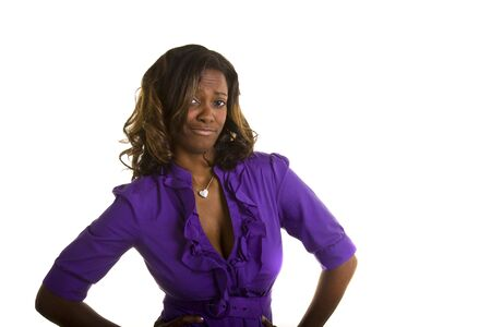 A black woman in a purple blouse showing some attitude with her hands on her hips