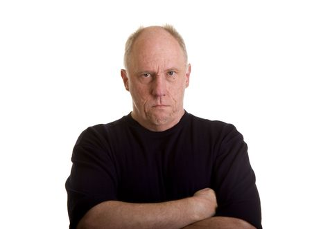 upset man: An older bald man in a black shirt looking angry or mad