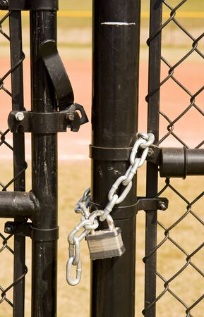 locked: A black chain link fence and an unlocked gate Stock Photo