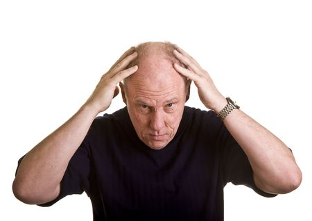hair loss: An older man leaning over with his hands on his bald head Stock Photo