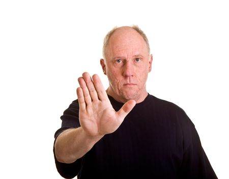 An older bald man holding his hand up in a stop gesture