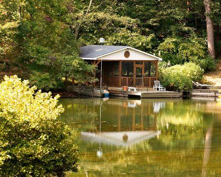 a nice house and boathouse on a placid lake Banco de Imagens