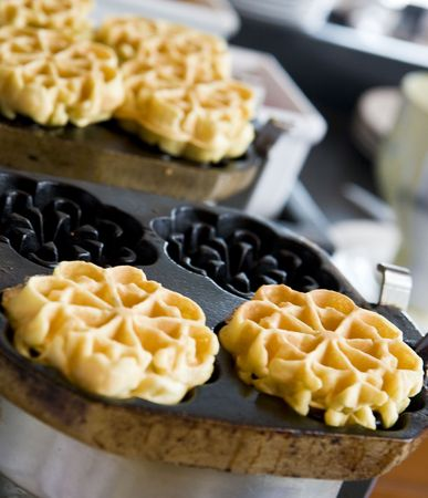 Fresh hot belgian waffles cooking in a waffle iron Фото со стока