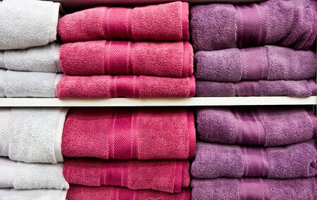 White and purple bath towels in a linen closet or a retail store
