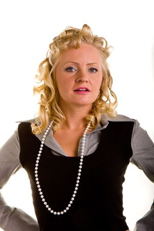 defiant: Woman with curly blonde hair and pearls with her hands on her hips and a defiant look