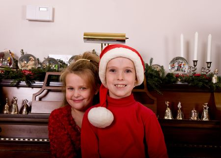 Two children sitting at a piano decorated for Christmas. The boy is wearing a santa hat photo