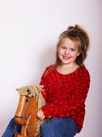 A little girl on a wooden rocking horse