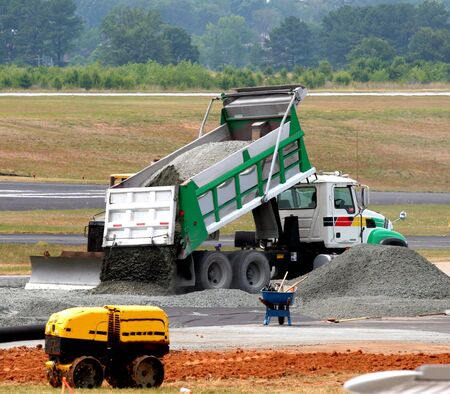 construction machinery: Dump truck dumping gravel on an airport construction site Stock Photo