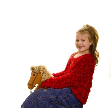 A young girl in red riding a toy rocking horse Stock Photo