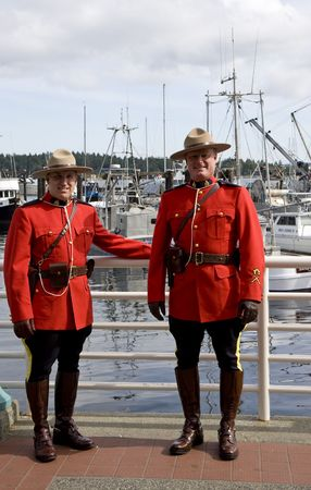 Two RCMP police in uniform at a local harbor for editorial use