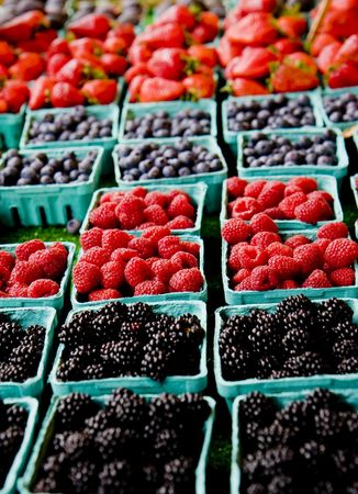 Four kinds of fresh berries in baskets in a fruit market Stock Photo - 4082282