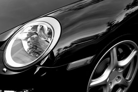 headlamp: Close up of headlight and fender of black German sports car Editorial