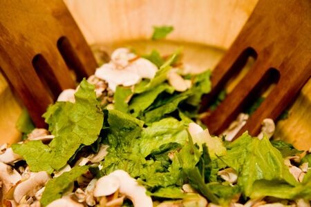 implements: A mixed salad in a wooden bowl with wooden implements