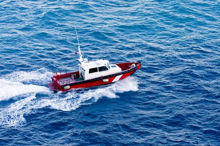 churning: A red and white pilot boat churning through the water of a bay