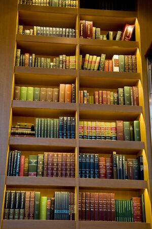 A tall shelf full of old books in a library