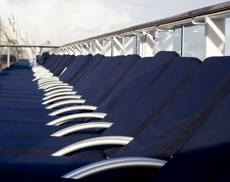 lined up: Blue chaise lounges lined up on the deck of a cruise ship