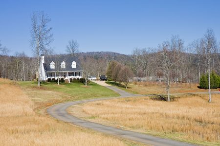 A nice white farmhouse down a long driveway across winter lawn 版權商用圖片