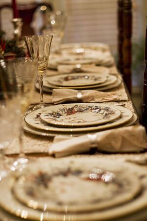 Formal china, crystal, and silver set out for a traditional family holiday dinner photo