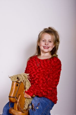 A young girl in a red sweater on a rocking horse