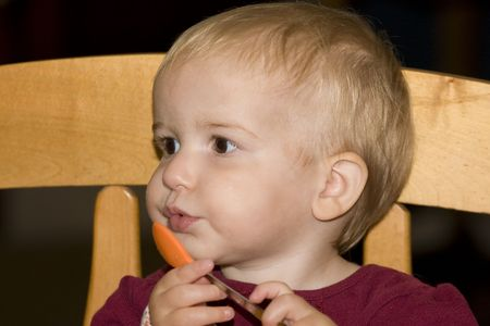 A young toddler with an orange spoon sitting in a high chair