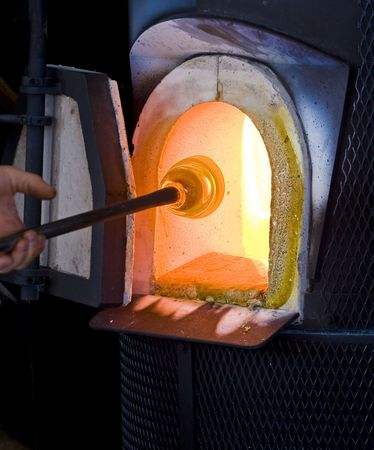 A glass Blower working molten hot glass in a furnace