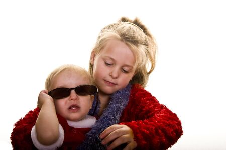 A young girl and a baby dressed in red playing with sunglasses photo