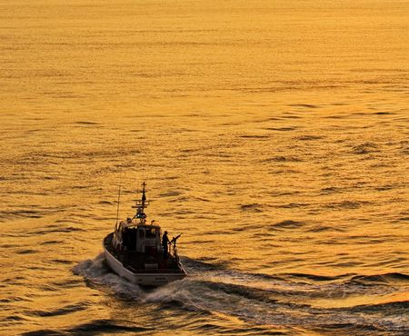 A coast guard cutter speeding across the bay at dusk Stock Photo - 4649830