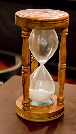 An old wood and glass hourglass on a table Banco de Imagens